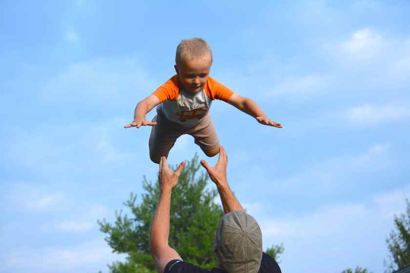 Eli, 3, lands in his Dad's hands after a flying high.